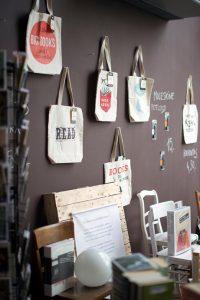 Draagtassen met opschiften over boeken aan een muur