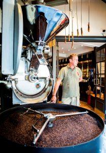 Man staat naast koffiebonen die gebrand worden in een ronde ton