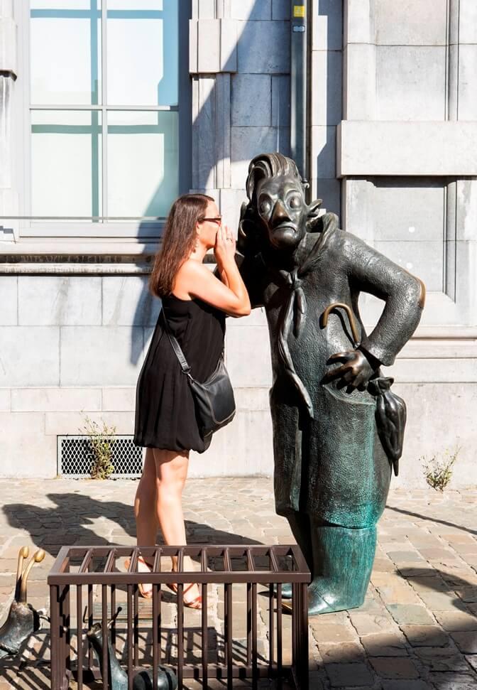Vrouw fluistert iets in het oor van bronzen standbeeld Djoseph et Francwes
