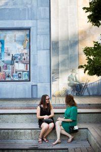 Twee vrouwen zitten op de trappen voor het fresco in Jardin du Mayeur