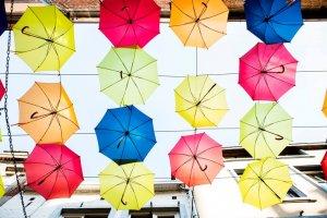 Onderaanzicht van gekleurde paraplu's aan kabels boven een straat