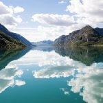 Het Gjendemeer in Noorwegen op een zonnige dag met wolken die weerspiegeld worden door het water