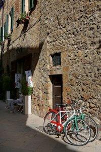 Straatje in Pienza met fietsen tegen de gevel.