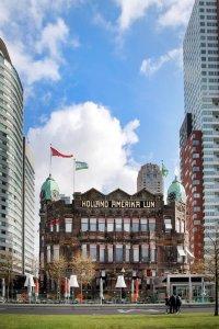 Gevel van Hotel New York in Rotterdam tussen wolkenkrabbers