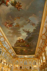 Met goud versierde zaal met een beschilderd plafond
