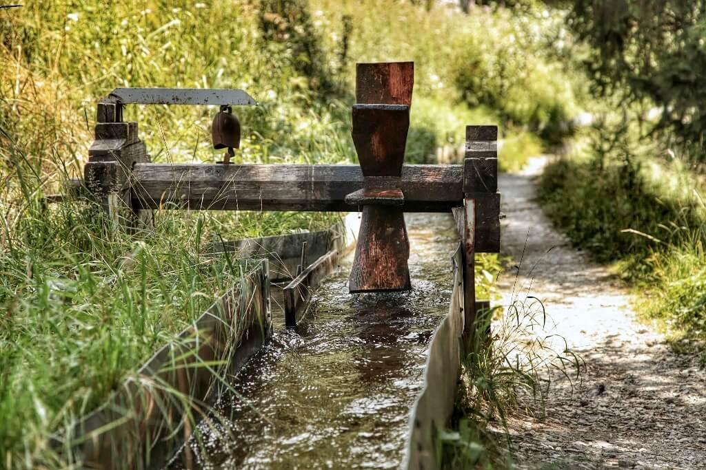 Een pad naast een oud irrigatiekanaaltje met een watermolentje