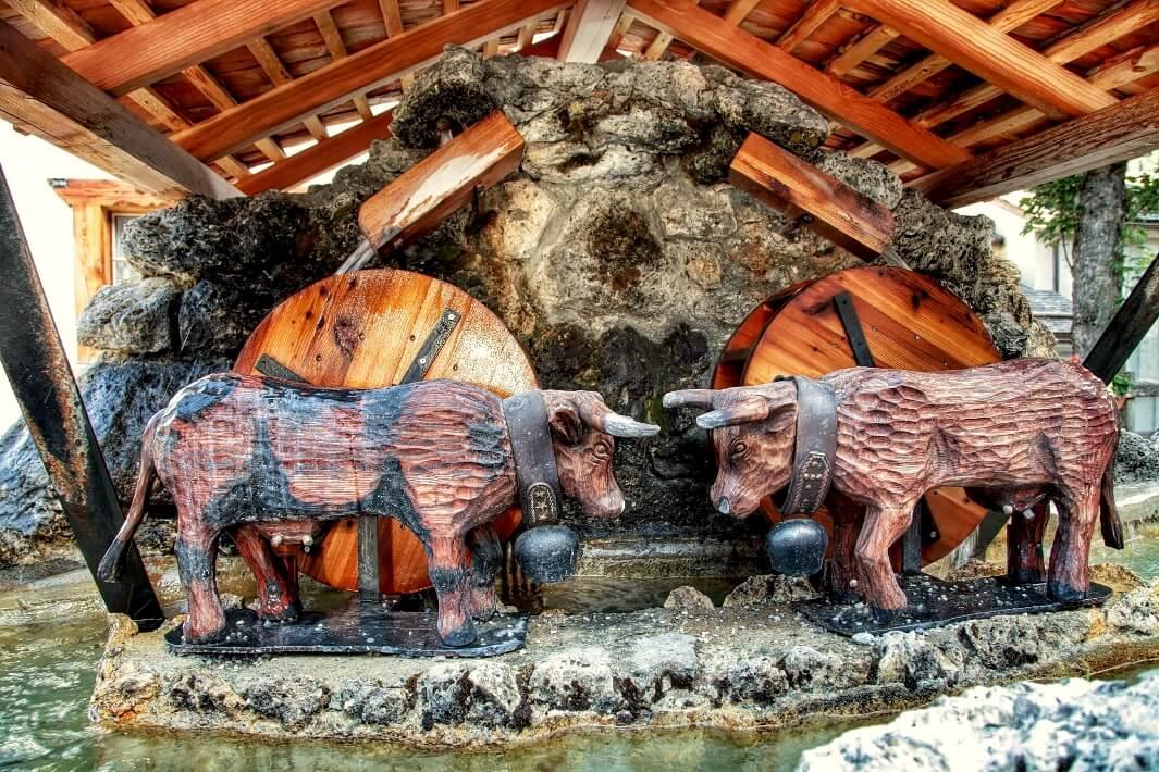 Twee houten koeien als versiering op een watermolen
