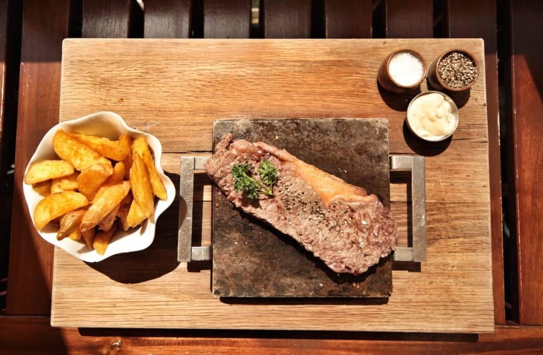 Houten plank met steak, bordje frietjes, schaaltjes mayonaise, peper en zout